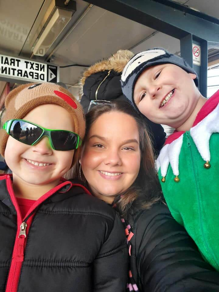 Elizabeth Dukart and sons in holiday clothing waiting for a train